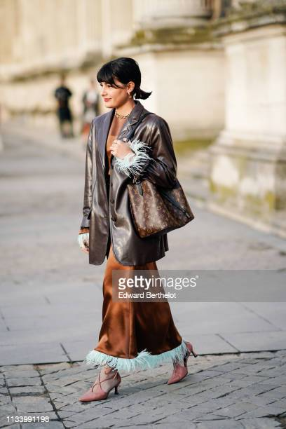 A guest wears a brown leather jacket a Vuitton bag a brown silky dress with fringes shoes outside Louis Vuitton during Paris Fashion Week Womenswear...