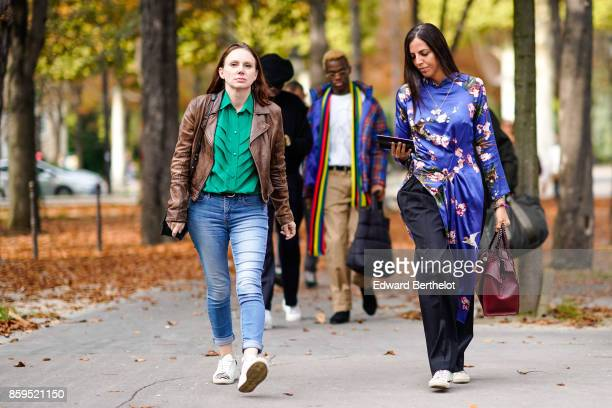 A guest wears a brown leather jacket an emerald green pleated shirtblue jeans white sneakers a guest wears a blue flower print long dress black baggy...