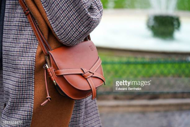 Guest wears a brown leather Loewe Gate bag, outside Chloe, during Paris Fashion Week - Womenswear Fall/Winter 2020/2021, on February 27, 2020 in...