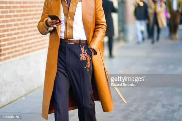 Guest wears a brown leather long coat, a shirt, a belt, suit pants with floral print, outside Fendi, during Milan Fashion Week Menswear Fall/Winter...