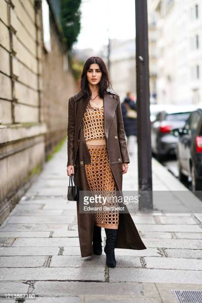 Guest wears a brown leather long coat with crocodile pattern, a mesh net dress, a Prada bag, black pointy high boots, outside Altuzarra, during Paris...