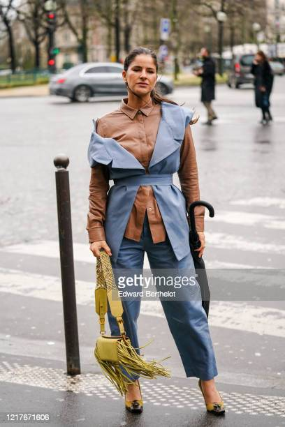 Guest wears a brown leather shirt, a blue sleeveless jacket, blue pants, a yellow bag with fringes, pointy shoes, outside Ann Demeulemeester, during...