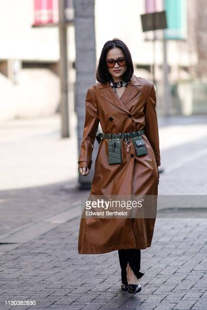 A guest wears a brown leather trench coat a green belt bag during London Fashion Week February 2019 on February 17 2019 in London England