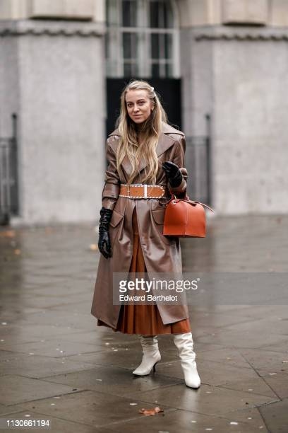 A guest wears a brown leather trench coat an orange bag a pleated skirt white boots during London Fashion Week February 2019 on February 18 2019 in...