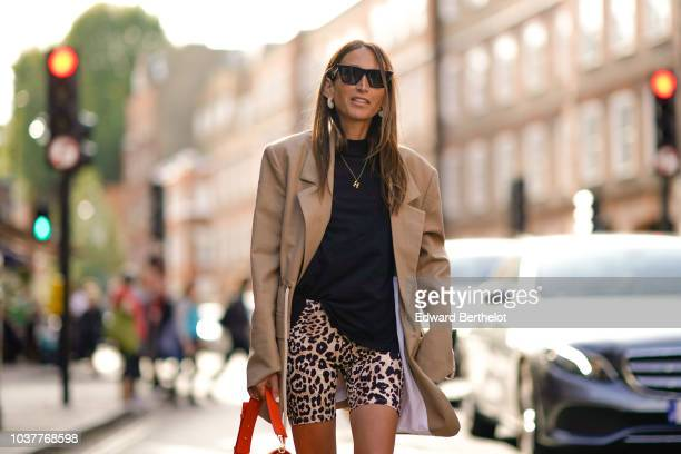 A guest wears a brown long blazer jacket a black top leopard print skirt an orange bag from JW Anderson during London Fashion Week September 2018 on...