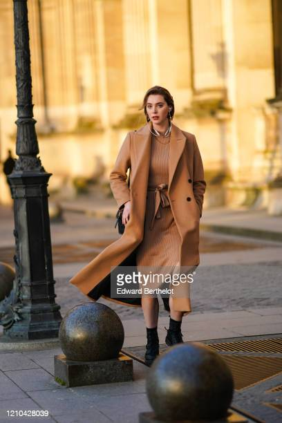 Guest wears a brown long coat, a striped dress, a necklace, a bag, outside Vuitton, during Paris Fashion Week - Womenswear Fall/Winter 2020/2021 on...