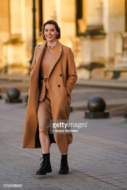 A guest wears a brown long coat a striped dress a necklace a bag outside Vuitton during Paris Fashion Week Womenswear Fall/Winter 2020/2021 on March...