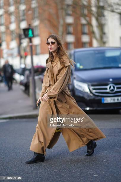 Guest wears a brown long trench coat, black leather pointy shoes, outside Lacoste, during Paris Fashion Week - Womenswear Fall/Winter 2020/2021 on...