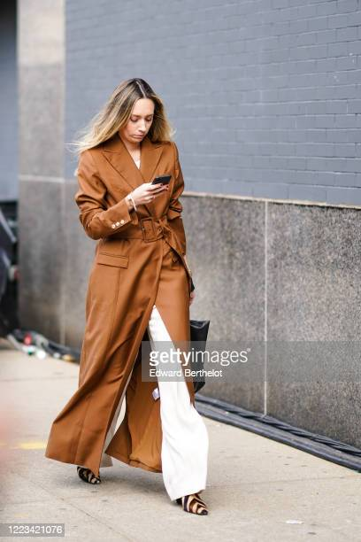 Guest wears a brown long trench coat, white flared pants, a bag, zebra print pointy shoes, outside Bevza, during New York Fashion Week Fall Winter...