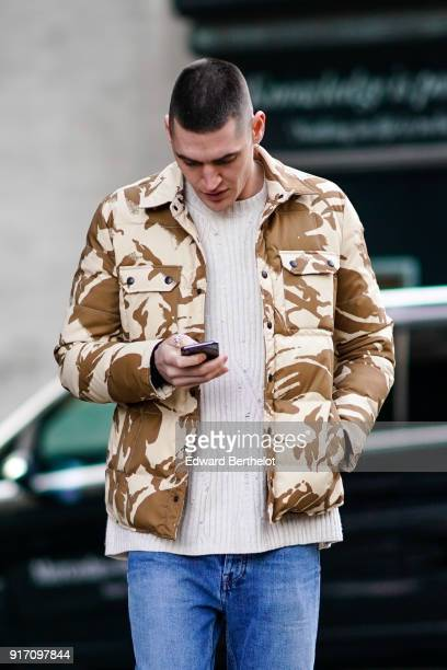 A guest wears a brown military cam print jacket a pull over during London Fashion Week Men's January 2018 at on January 6 2018 in London England
