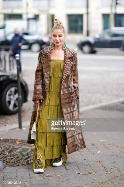 A guest wears a brown printed geometric pattern coat a green khaki dress a Saint laurent bag outside Miu Miu during Paris Fashion Week Womenswear...