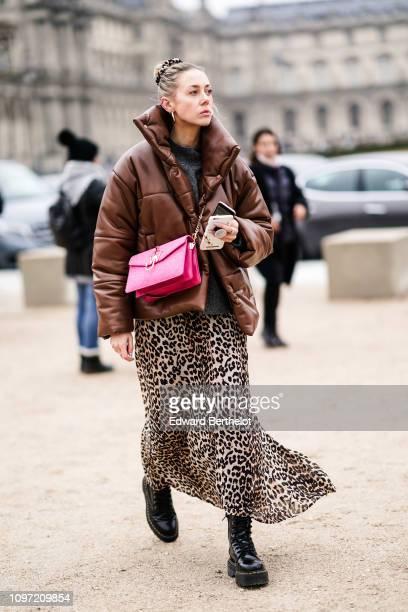 Guest wears a brown puffer jacket, a pink JW Anderson bag, leopard print dress, outside Kenzo, during Paris Fashion Week - Menswear F/W 2019-2020, on...