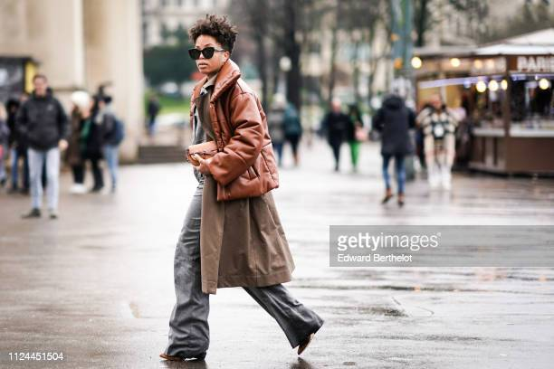 A guest wears a brown puffer jacket gray flare pants a Loewe bag outside Elie Saab during Paris Fashion Week Haute Couture Spring Summer 2020 on...