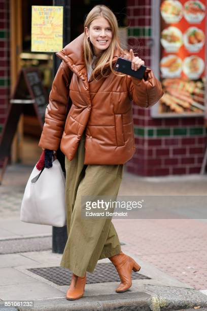 A guest wears a brown puffer jacket green khaki pants brown shoes during London Fashion Week September 2017 on September 16 2017 in London England