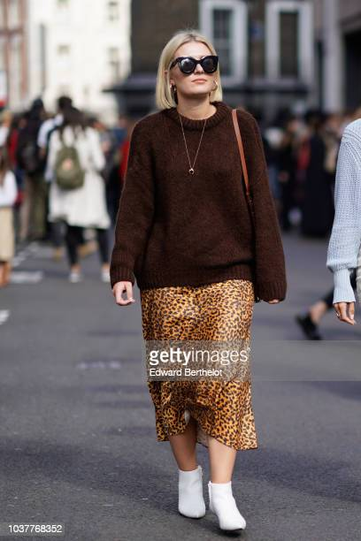 A guest wears a brown pullover a leopard print skirt white shoes during London Fashion Week September 2018 on September 15 2018 in London England