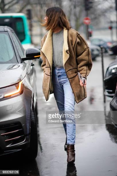 A guest wears a brown sheepskin jacket a grey sweater blue jeans brown boots outside Balmain during Paris Fashion Week Womenswear Fall/Winter...