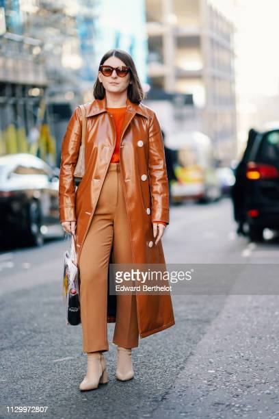 A guest wears a brown shiny coat a brown pants an orange pullover during London Fashion Week February 2019 on February 15 2019 in London England