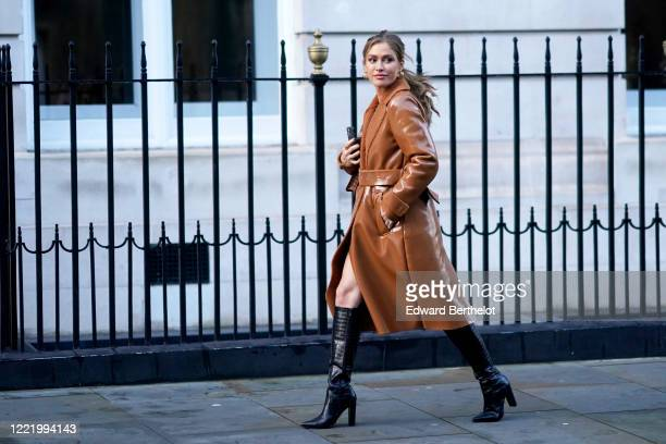 A guest wears a brown shiny vinyl long coat black leather crocodile high heel pointy boots earrings during London Fashion Week Fall Winter 2020 on...