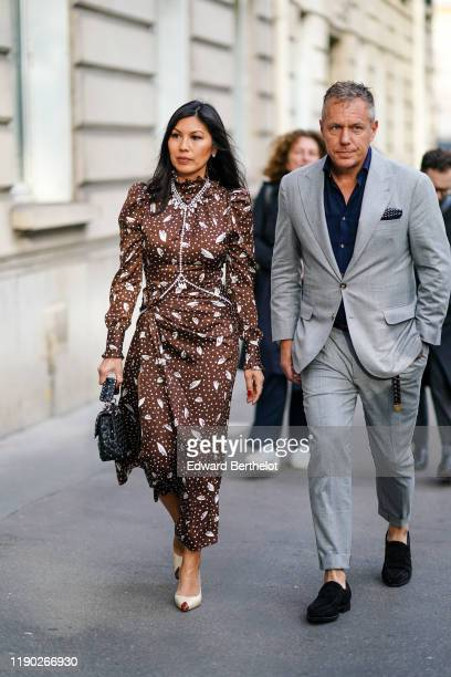 Guest wears a brown silky lustrous dress with printed polka dots, pointy shoes, a necklace, a studded bag, outside Alessandra Rich, during Paris...