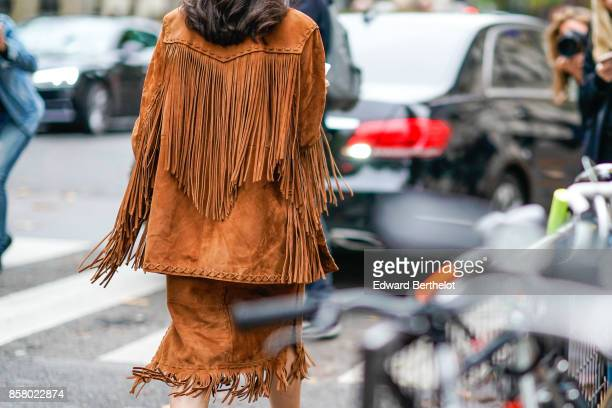 A guest wears a brown suede coat with fringes outside Valentino during Paris Fashion Week Womenswear Spring/Summer 2018 on October 1 2017 in Paris...