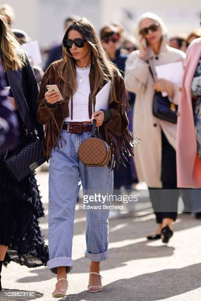 A guest wears a brown suede fringed jacket a Vuitton monogram bag blue jeans outside Dior during Paris Fashion Week Womenswear Spring/Summer 2019 on...