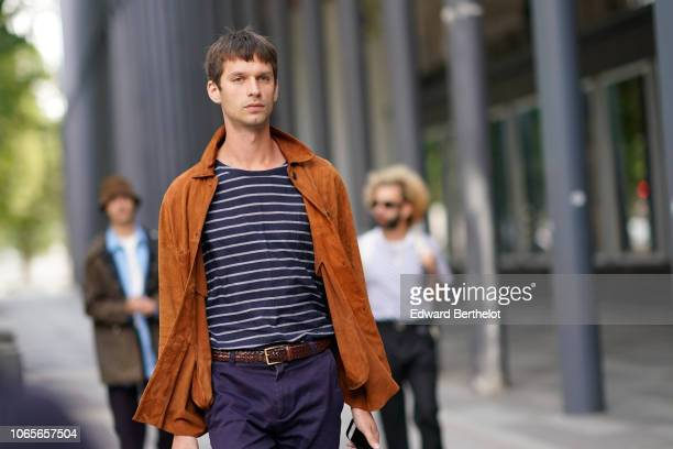 A guest wears a brown suede jacket a black and white striped tshirt a brown leather belt outside Issey Miyake during Paris Fashion Week Menswear...