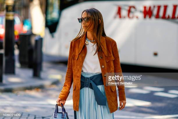 A guest wears a brown suede jacket a white top a blue pleated skirt a blue bag during London Fashion Week September 2018 on September 17 2018 in...