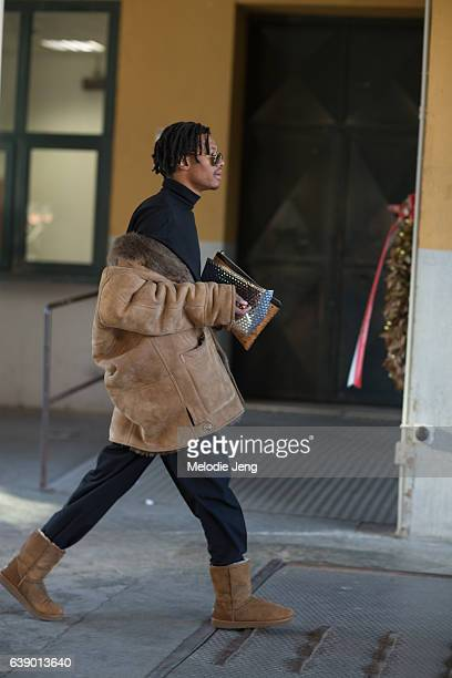A guest wears a brown suede jacket off his shoulders during Milan Men's Fashion Week Fall/Winter 2017/18 on January 16 2017 in Milan Italy