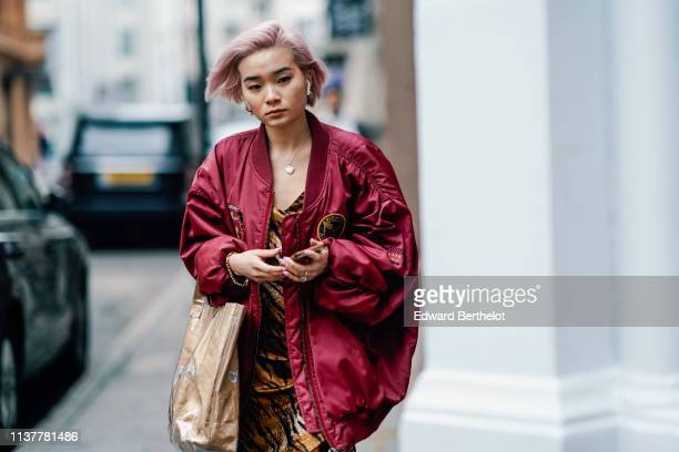 A guest wears a brown tiger print dress a transparent tote bag a lustrous burgundy bomber jacket during London Fashion Week February 2019 on February...