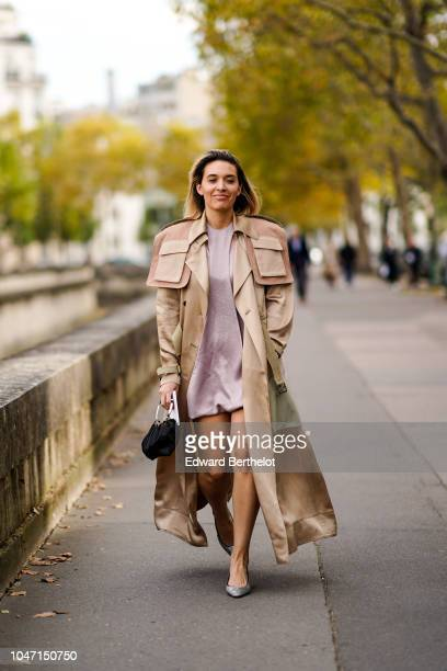 A guest wears a brown trench coat a pale purple dress a black bag shoes outside Valentino during Paris Fashion Week Womenswear Spring/Summer 2019 on...