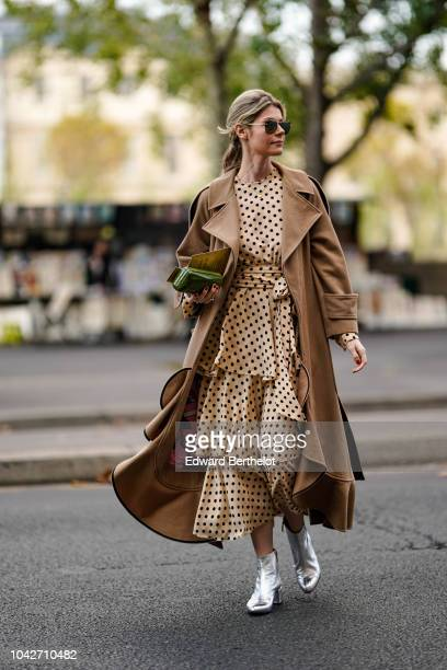 A guest wears a brown trench coat a ruffled polka dots dress silver shoes outside Andrew GN during Paris Fashion Week Womenswear Spring/Summer 2019...