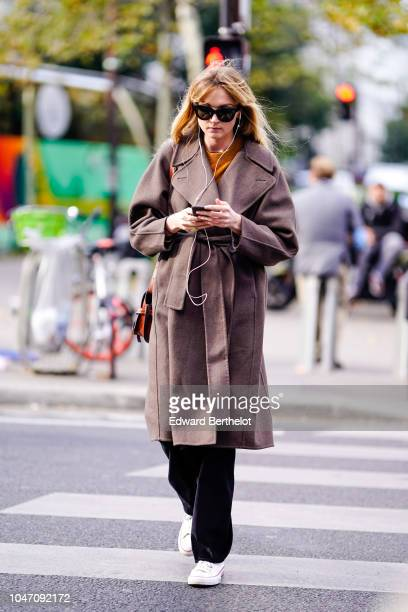 A guest wears a brown trench coat black pants white sneakers shoes outside APC during Paris Fashion Week Womenswear Spring/Summer 2019 on October 1...