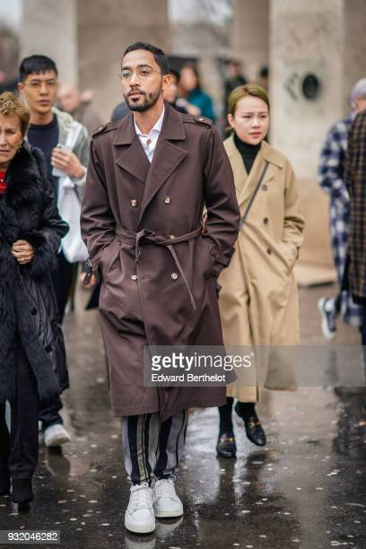 A guest wears a brown trenchcoat black and grey striped pants white sneakers during Paris Fashion Week Womenswear Fall/Winter 2018/2019 on March 4...