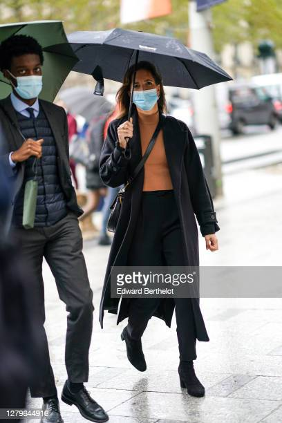 A guest wears a brown turtleneck pullover a black coat black pants boots outside Miu Miu during Paris Fashion Week Womenswear Spring Summer 2021 on...