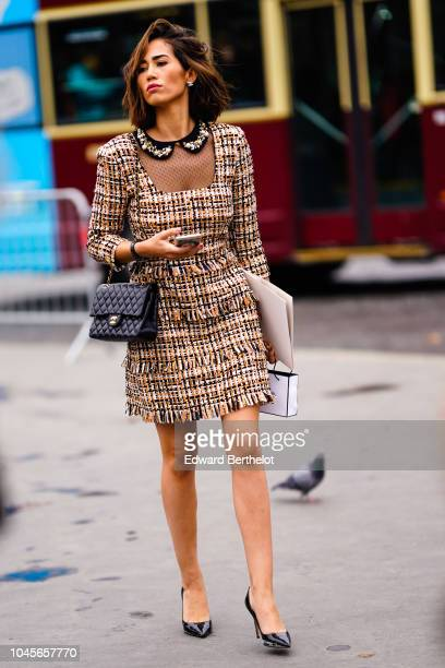 A guest wears a brown tweed dress a black Chanel bag outside Chanel during Paris Fashion Week Womenswear Spring/Summer 2019 on October 2 2018 in...