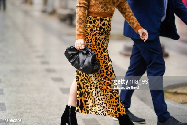 A guest wears a brown wool checked pullover a black leather Bottega Veneta bag brown leopard print skirt outside Miu Miu during Paris Fashion Week...