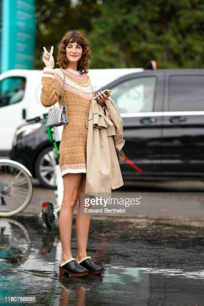 A guest wears a brown wool dress with printed patterns a silver quilted Chanel bag black leather shoes holds a trench coat outside Chanel during...