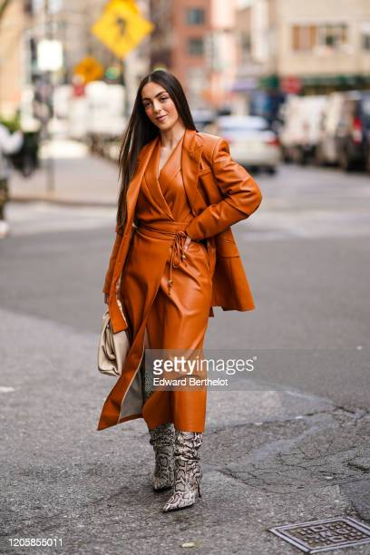 Guest wears a brown/orange leather jacket, a leather dress, gray snake pattern pointy boots, during New York Fashion Week Fall Winter 2020, on...