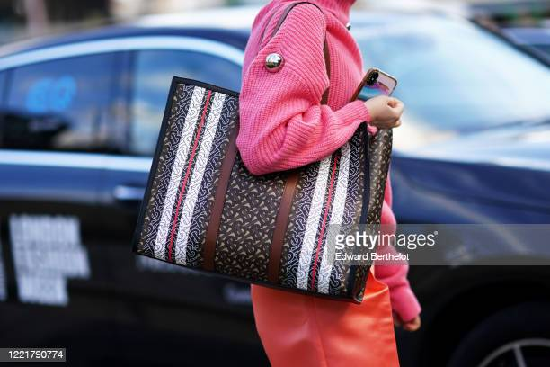 A guest wears a Burberry monogram bag a pink wool pullover orange pants during London Fashion Week February 2020 on February 17 2020 in London England
