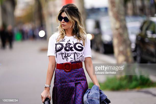 A guest wears a burgundy belt a DG logo white tshirt from Dolce Gabbana a purple glitter skirt sunglasses outside Issey Miyake during Paris Fashion...