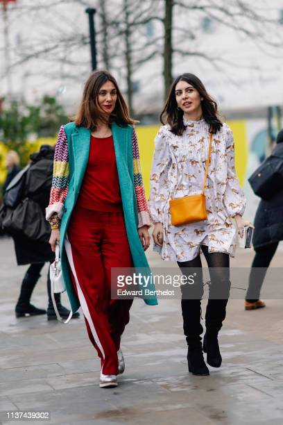Guest wears a burgundy sweat shirt, burgundy sport pants, a turquoise blue coat with colorful sleeves, colorful wristlets, a white alligator pattern...