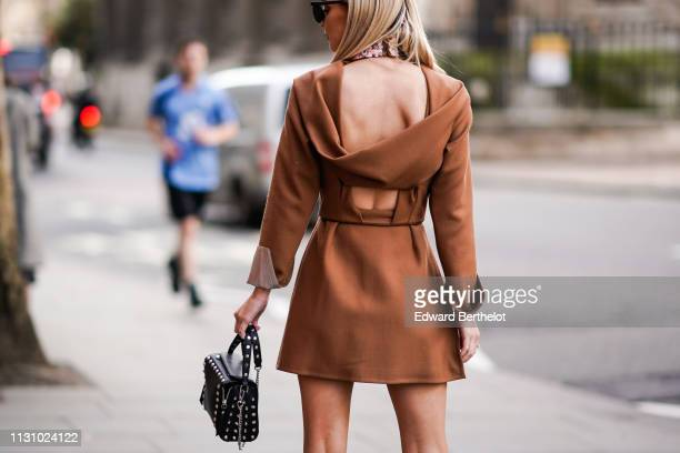 Guest wears a camel bare back dress, a black studded bag, during London Fashion Week February 2019 on February 19, 2019 in London, England.