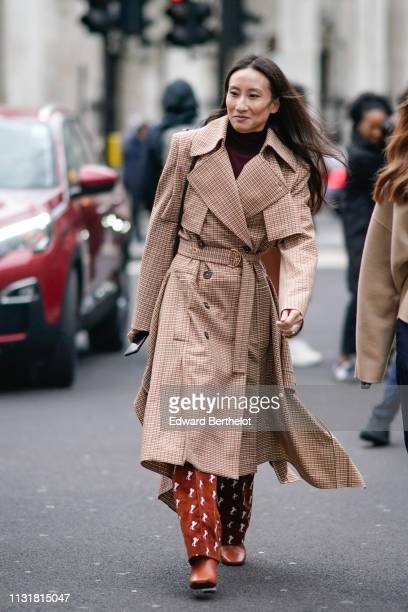 A guest wears a camel checkered doublebreasted trench coat white lions pattern red pants brown boots during London Fashion Week February 2019 on...