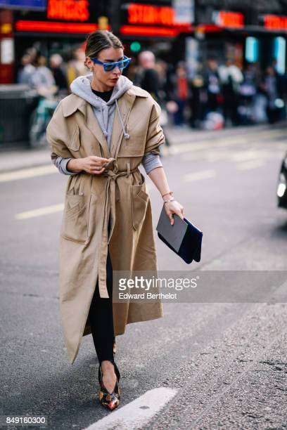 A guest wears a camel coat blue sunglasses outside Topshop during London Fashion Week September 2017 on September 17 2017 in London England
