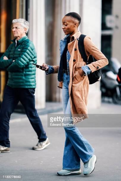 A guest wears a camel corduroy coat a blue denim pantsuit with flare pants grey studded Nike sneakers a black backpack outside CDG Comme des Garcons...