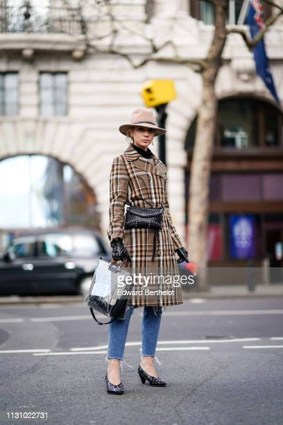 A guest wears a camel hat earrings a brown checkered coat a black studded bag studded black gloves studded black pumps ripped hem jeans during London...