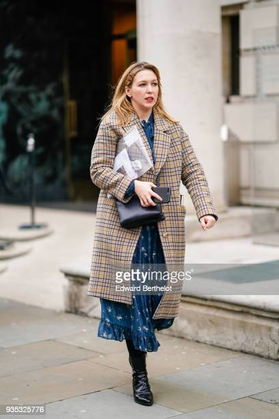 A guest wears a camel princeofwales checkered coat a blue flowy dress with flounce at the end a black handbag black boots during London Fashion Week...