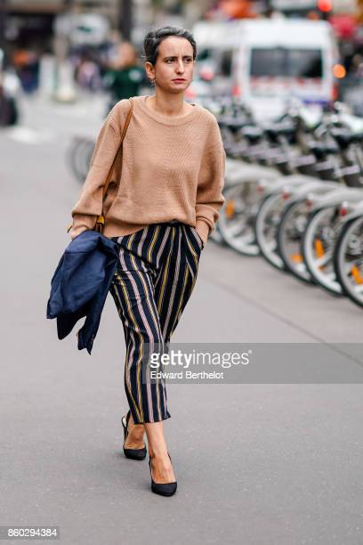 A guest wears a camel pullover navy blue and camel striped pants navy blue shoes outside the Dries Van Noten show during Paris Fashion Week...