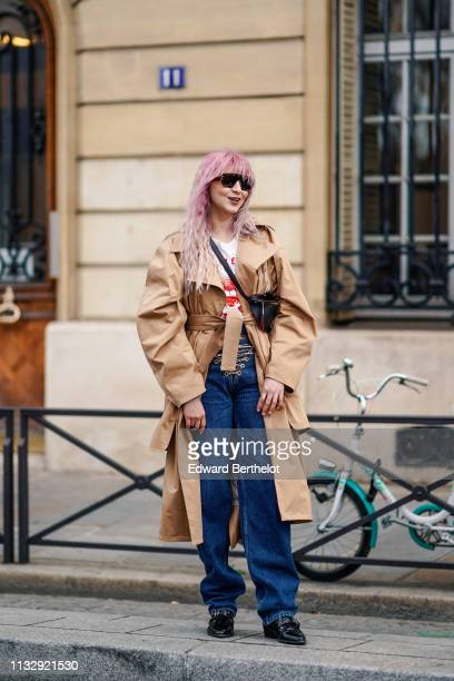 A guest wears a camel trench coat a black beltbag blue jeans laced up with a golden chain black shoes outside Y/Project during Paris Fashion Week...