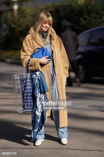 A guest wears a camel wrap coat a blue denim overalls a blue studded handbag a large transparent plastic tote bag a blue and white large scarf white...